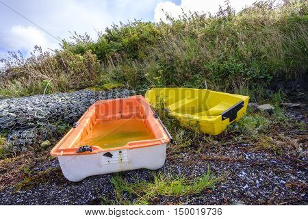 Two colorful orange and yellow small boats on a stone shore filled with rainwater