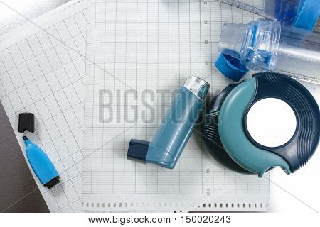 Asthma relief concept salbutamol inhalers aerosol medication and paper on chrome background