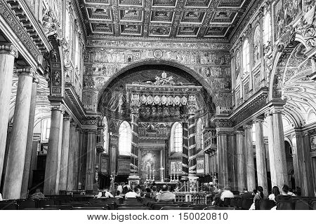 ROME, ITALY - JULY 11, 2015: Interiors of Basilica of St. Mary Major features beautiful and old mosaics. The decorated Triumphal Arch at the head of the nave, people at the foreground. Black and white