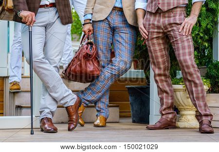 Stylish men in trendy suit with a walking stick and  leather valise stand on the terrace in summer