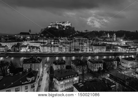 View of Salzburg, Austria at night. Illuminated Castle at the background, reflection in the river. Dark sky. Black and white