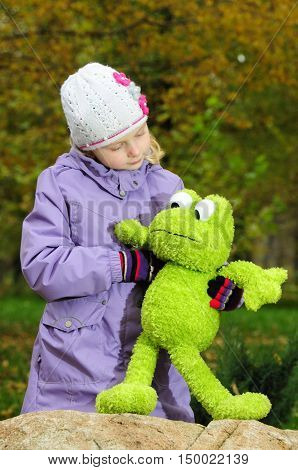 child outdoors with a toy green frog in autumn