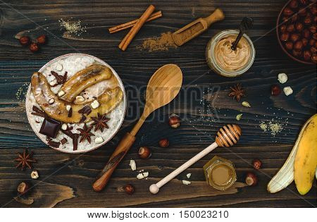 Preparing healthy fall and winter breakfast bowl. Chai tea infused overnight oats tahini porridge topped with caramelized bananas raw dark chocolate and hazelnut butter. Overhead top view flat lay. Rustic country style. Ideal Christmas morning meal concep