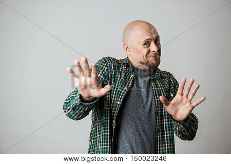 Handsome emotional man in shirt showing stop over beige background. Copy space.