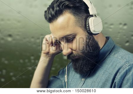 A bearded man in a denim shirt listens to music through white headphones. Guy with a pensive expression face. The event occurs on a green blurred background.