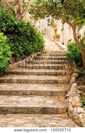 Stairs in S-curve shape in old historic street of Tossa de Mar Costa Brava Catalonia Spain. Late summer photo.