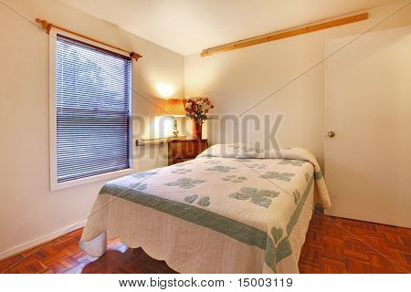 Bedroom With White Walls And Cherry Hardwood Floor