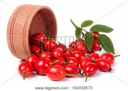 rosehip berries in a wooden bowl isolated on white background.