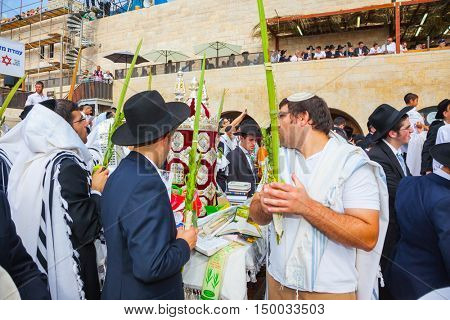 JERUSALEM, ISRAEL - OCTOBER 12, 2014:  The area in front of Western Wall of Temple filled with people. The Jews of ritual clothes - tallit hold four plants on Sukkot. Morning autumn Sukkot