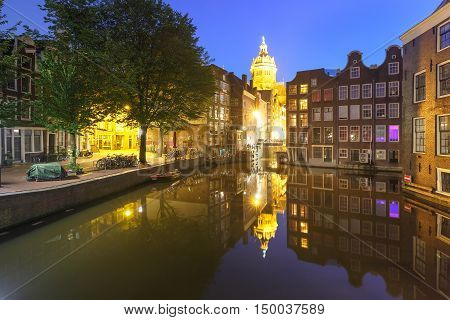 Night red-light district De Wallen, canal Oudezijds Voorburgwal, bridge, Basilica of Saint Nicholas and its mirror reflection, Amsterdam, Holland, Netherlands. Long exposure.