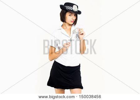 Young girl brunette with pretty smiling face in sexy police officer uniform black cap holding iron wristbands in hands posing on white background isolated
