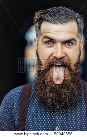 young handsome bearded man portrait with long beard and moustache has stylish hairdo in shirt outdoor showing tongue on grimace face