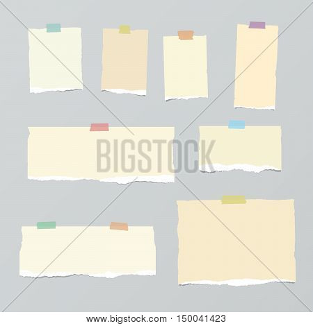 Pieces of light brown torn note paper with colorful adhesive, sticky tape stuck on grey background.