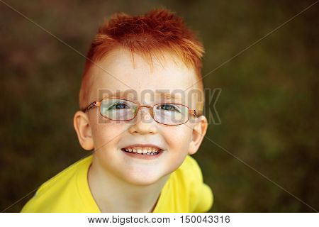 Happy Baby Boy With Red Hair In Glasses