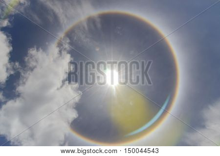 Sun with circular rainbow sun halo occurring due to ice crystals in atmosphere in thailand