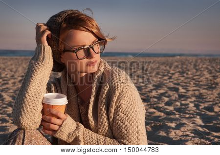 Beautiful view of ocean happy woman in a knitted cardigan in a glasses sitting on the beach in autumn drinking coffee