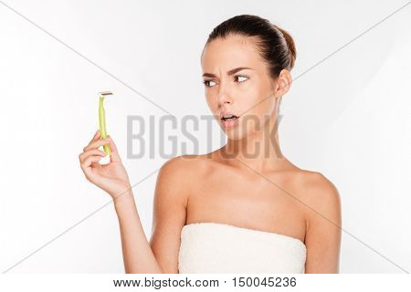 Young beautiful woman with pure skin in a towel holding razor blade preparing to shave isolated on white background