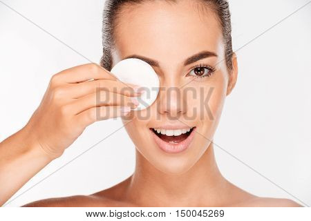 Laughing beautiful young woman holding round white cotton pad to her eye isolated on a white background