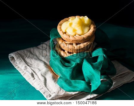 Shortcrust tartlets with lemon curd stacked on beige napkin on dark green and black background