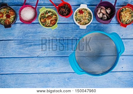 Scrambled eggs baked with fillings in mini ceramic forms, spices and strainer