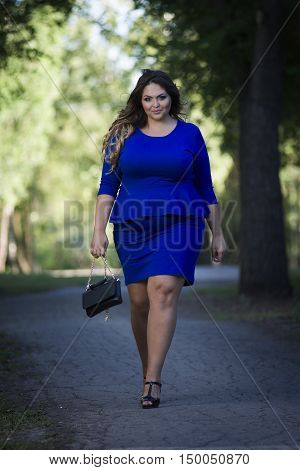Young beautiful caucasian plus size fashion model in blue dress outdoors xxl woman on nature full length portrait
