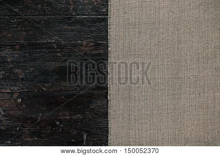 Texture image: dark wood table half covered with linen tablecloth