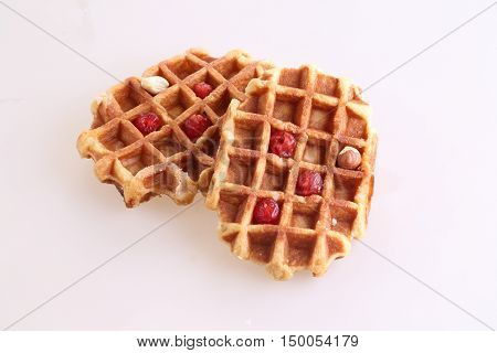 Sweet Belgian waffle with dried cranberries and nuts on white background