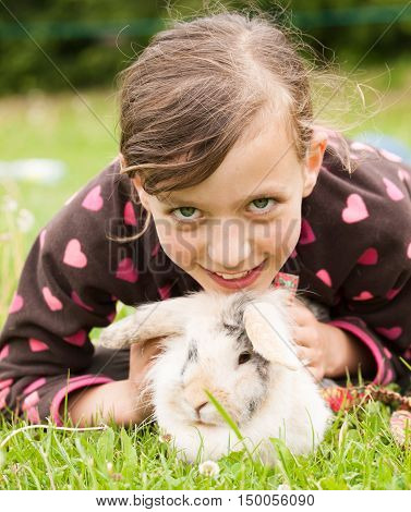 Young girl lying on meadow with her rabbit