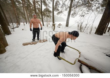 Two bare-chested guys do exercises with homemade wooden sports equipment at outdoor sportsground in winter wood.