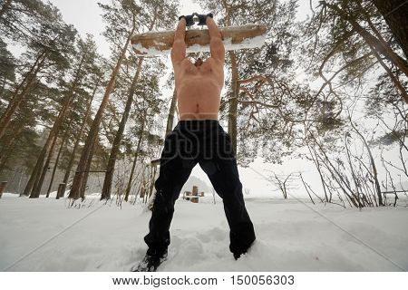 Bare-chested guy works with wooden heavy load on sportsground at winter snowy forest.