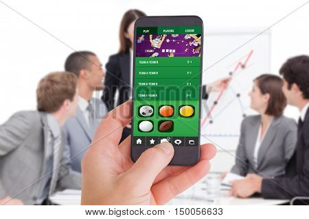 Female hand holding a smartphone against assertive businesswoman giving a presentation
