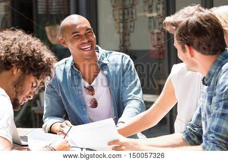 Cheerful college students studying together for next exam. Group of multi ethnic friends smiling and taking notes. Education concept.