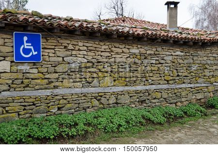 invalid parking sign on old stone wall