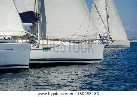 Sailing boats bows near the regatta start line. Racing on the cruising yachts in the Mediterranean. Sardinia island, Italy.