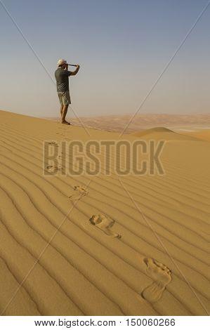 Man looking through spyglass in a desert