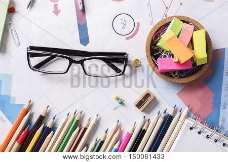 Top view of messy office workplace with colorful supplies financial reports and glasses