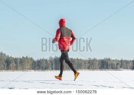 Running sportsman in protective sportswear is making winter training session outdoors