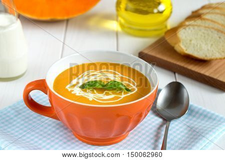 Squash Soup With Cream In A Bowl On The Wooden Table.