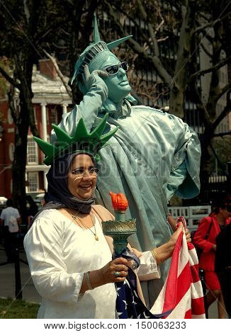 New York City - August 22 2004: Statue of Liberty Mime poses with a visiting Muslim woman holding an American flag in Battery Park