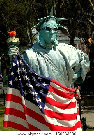 New York City - August 22 2004: Statue of Liberty mime holding an American flag and torch in Battery Park