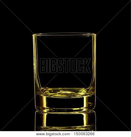 Silhouette of yellow strong liquor classic glass with clipping path on black background.