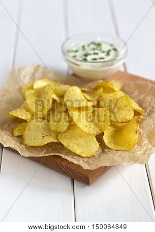 Potato Chips On A Parchment With A Dipping Sauce On A White Table.