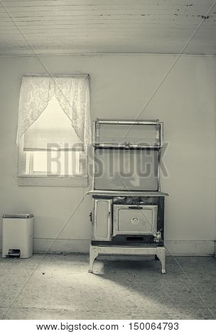 vertical image of an old cook stove sitting in an empty kitchen beside a window with a vintage layer added to give it an old yellowed look.