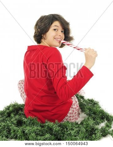 A pretty young teen in pajamas looking back and the viewer as she prepares to eat her peppermint log.  On a white background.