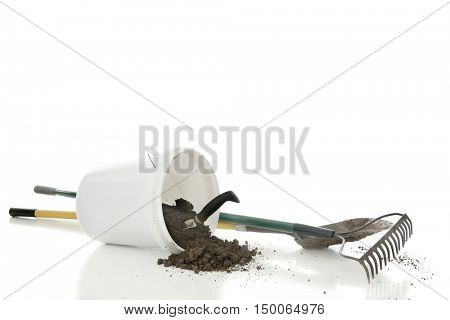 A white bucket of spilled dirt with a hand spade.  A dirty garden rake and shovel nearby.  On a white background with  space above for your text.