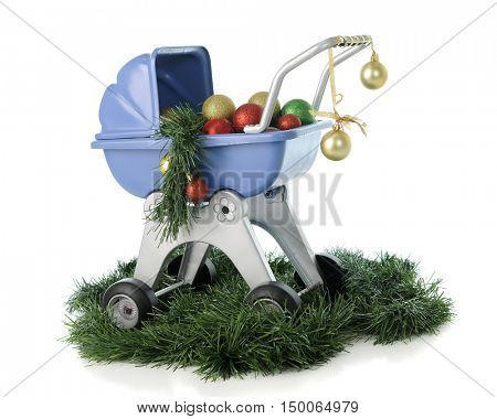 A child's blue doll buggy surrounded by Christmas garland and filled with colorful ornaments.  On a white background.