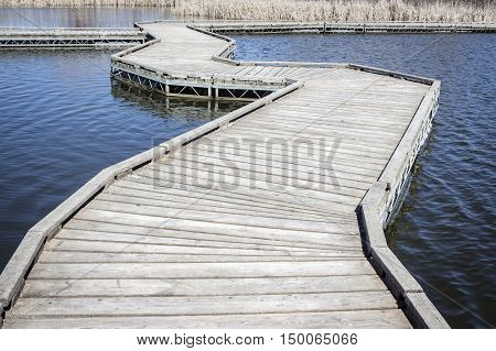 horizontal image of a curving floating walking bridge floating across the pond in the summer.