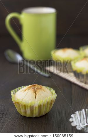 Homemade cakes-volcano on the table with green cup of tea spoon and empty bakeware.