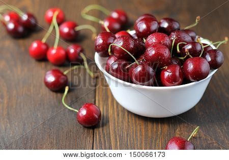 Sweet Cherries In The White Bowl On The Wooden Table.