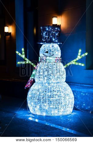 Luminous Christmas Snowman made of blue electric garland in the dark
